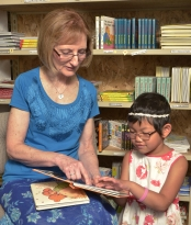 Photo of Debra Bonde and a little girl reading braille together