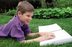 Photo of a child reading a braille book outside
