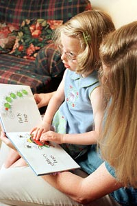 Photo of Girl with Mother Reading Braille Book.
