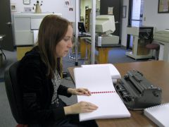 Photo of a Seedlings volunteer proofreading a book
