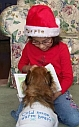image of child in Santa hat showing her book to her dog