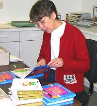 Photo of a Seedlings volunteer assembling print-and-braille books