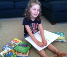 Photo of Lizzy reading braille books