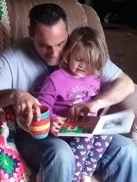 Photo of child and father reading a Seedlings book